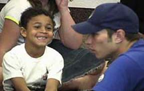 An image of a smiling boy talking with a SKITuations actor in a small group discussion time.