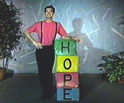 A man in a red shirt stands beside stacked boxes that spell HOPE.