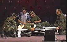 "A depiction of a scene from the TV show ""MASH"" with four characters, in Army uniforms, caring for an injured person on a stretcher."