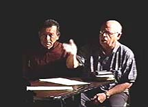 Two men sit and talk with one man gesturing.