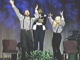 A woman holds a book and two mimes in striped shirts leap up with their hands raised.