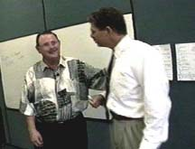 A man talks with another man in a white shirt and tie.