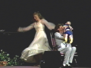 A dancer in white flowing dress, dances beside a woman, on a rocking chair, holding a baby.