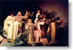 A group of adults and children, dressed in Bible costumes, pointing to something.