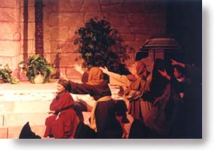 A group of people gesturing with both arms toward an open tomb.