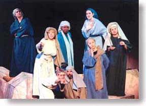 A group of people in Bible costumes pointing at something.