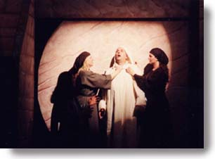 Lazarus comes out of the tomb with Mary and Martha at his side.