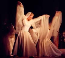 Women, dressed in flowing white outfits, dancing as Angels.