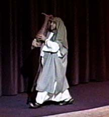 A man, dressed in Bible costume, carrying a water pot.