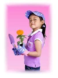 A cute 10 year old girl holding a marigold flower and a garden shovel.