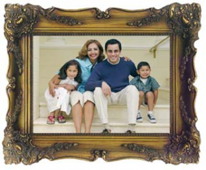 A framed image of a family sitting on the steps of their home.