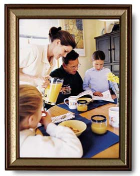 A framed picture of a family reading a SKITuations script for children's church at the breakfast table.