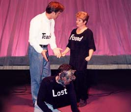 "An image from the play, ""God, Look!"" in which the ""Teacher"" motions to ""Lost,"" while ""Found"" looks on."