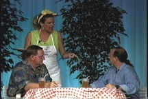 A woman, holding a waitress tray, talks with two men sitting at a table with a checkered table cloth.
