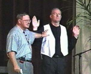 A man in a blue shirt points to a man with a vest on.