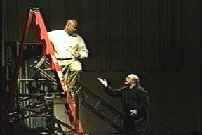 A man on a ladder listens to a man gesturing on the floor below him.