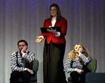 A woman holds a book, and gestures to two mimes in striped shirts.