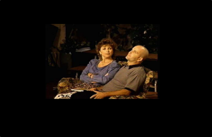 A man and a woman sitting on chairs discussing something.