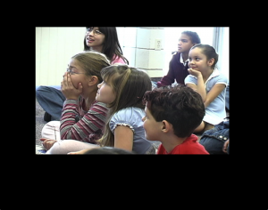 A group of children paying attention to something interesting.