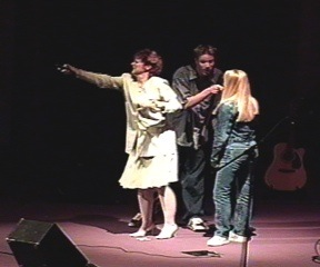 An adult woman using a remote, with two teens arguing behind her.