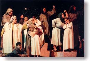 An angry group of people, dressed in Bible costumes, shaking their fists and yelling.