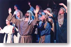 A group of adults and children in Bible costumes with their hands lifted in worship.