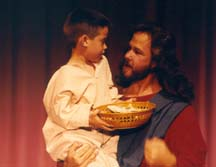Jesus holding a young boy with a basket of food.