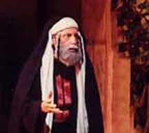 A older man, dressed in High Priest garments, depicting Caiaphas, the High Priest.