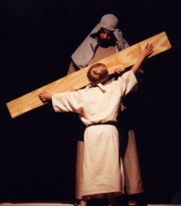 A small boy measuring a board held by a man dressed in Bible costumes.