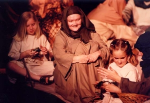 A woman and two children, dressed in Bible costumes, during a rehearsal break.