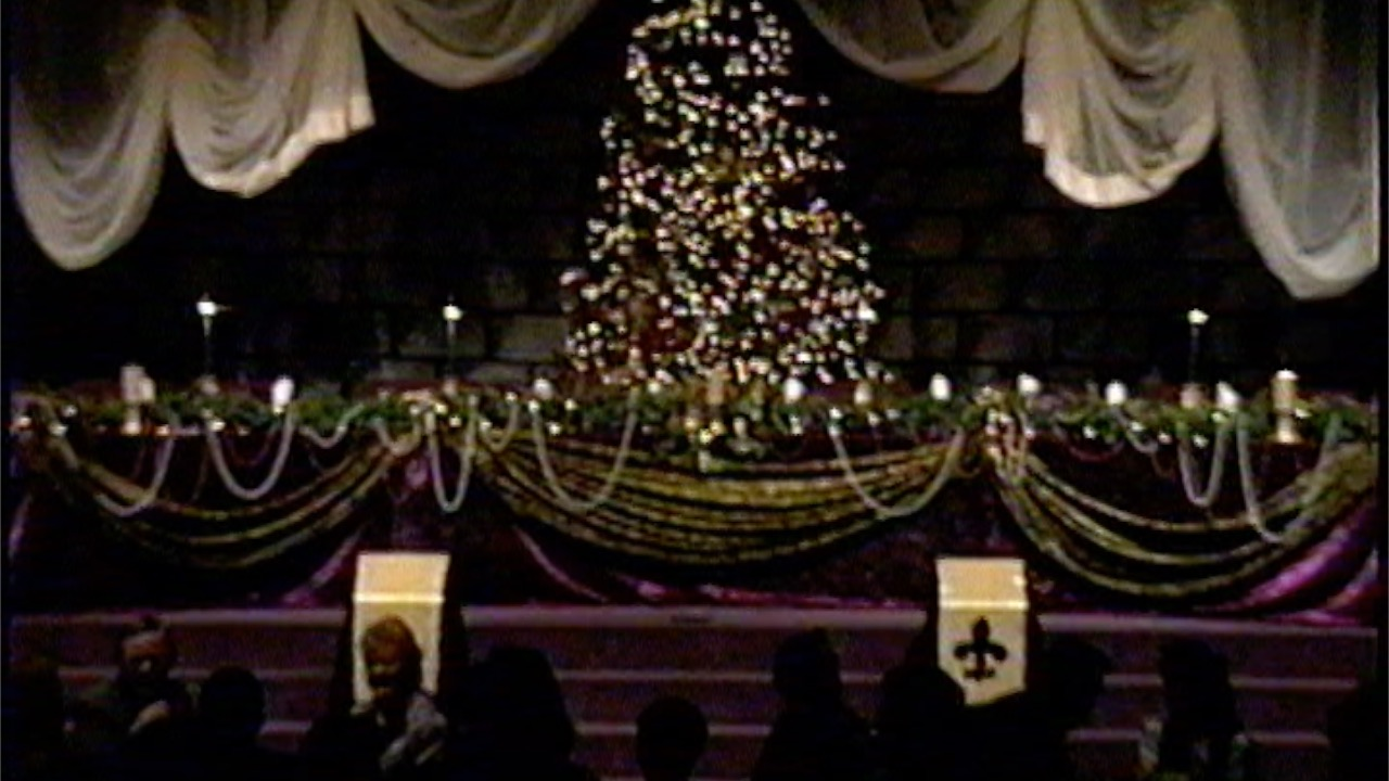 A Christmas tree on a church stage with elegantly decorated decorations and curtains.