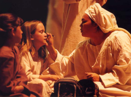 A woman putting makeup on a girl, dressed in Bible costumes.