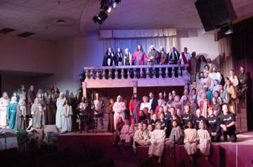 "A wide shot of the full cast of ""God's Masterpiece."""
