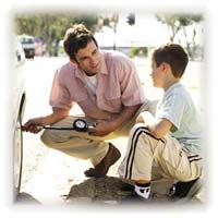 A man teaching his son how to check the air pressure in a car tire.