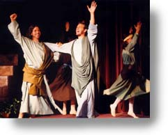Men actors, in Bible Costumes, on stage, celebrating with hands raised.