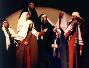 Men, dressed in Bible costumes depicting Scribes and Pharisees arguing about Jesus.