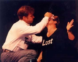 "The character ""Teacher"" wipes the character ""Lost's"" forehead with a cloth."