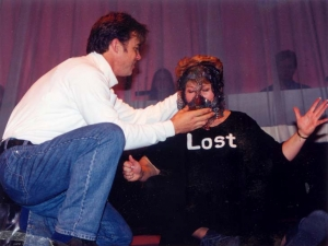"The character ""Teacher"" removes the mask from the character ""Lost's"" face."
