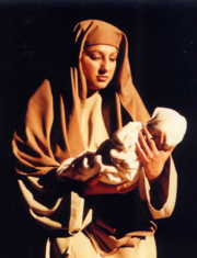 A woman, dressed in Bible attire, holding a baby.